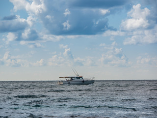 sport fishing boat in the sea. beautiful cloudy sky
