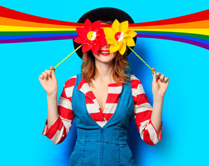 smiling red-haired white european woman in hat and red striped shirt with jeans dress with two pinwheels on blue background and with rainbow