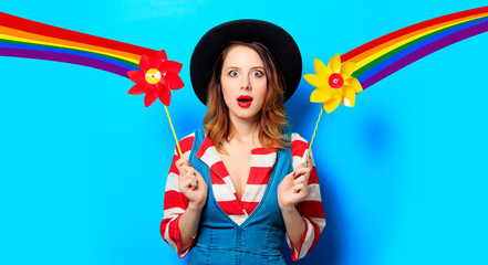 Portrait of young surprised red-haired white european woman in hat and red striped shirt with jeans dress with pinwheel on blue background and with rainbow