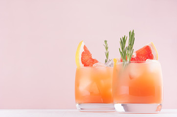 Cold lemonade of fresh grapefruit juice, alcohol and ice cubes decorated slice citrus and twig rosemary on fashion pastel pink background.