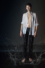 Attractive young man in white wet clothes in small pool under drops of the rain. Studio photo