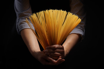 Woman's hands with gluten free spaghetti made from rice and maize on dark background