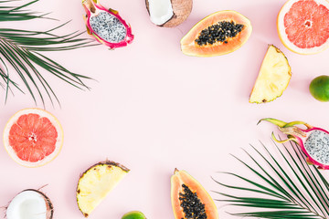 Summer fruits. Tropical palm leaves, pineapple, coconut, papaya, dragon fruit, orange on pastel pink background. Flat lay, top view, copy space
