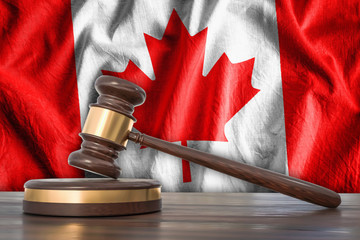 Wooden gavel and flag of Canada on background - law concept