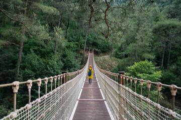 Woman with raincoat walikng on suspension bridge
