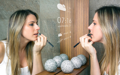 Smart mirror concept. Young woman applying lip liner in front of a smart mirror that gives information