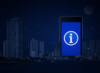 Information sign icon on modern smart phone screen over office city tower, river and fantasy night sky, Customer support concept