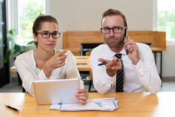 Business colleagues pointing at something and using devices. Woman using tablet computer and man talking on smartphone with blurred office interior in background. Business people attention concept.