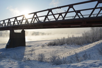 Bridge over the river, which does not freeze, in sunny winter day.