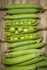 fresh peas on a kitchen wooden table