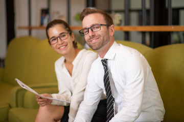 Smiling coworkers sitting on couch in office lobby. Business man and woman looking at camera and holding document. Business coworkers concept.