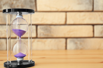 Hourglass on wooden table. Time management concept