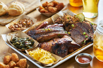 Poster Grill / Barbecue texas style bbq tray with smoked brisket, st louis ribs, pulled pork, chicken, hot links, and sides