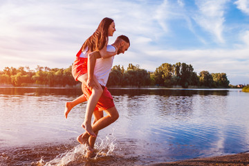Young man and woman running on summer river bank. Couple having fun at sunset. Guys chilling Wall mural