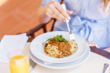 Young happy woman sitting at the table in cafe and enjoying the meal. Hungry woman eating tasty pasta. Dish of spaghetti Bolognese