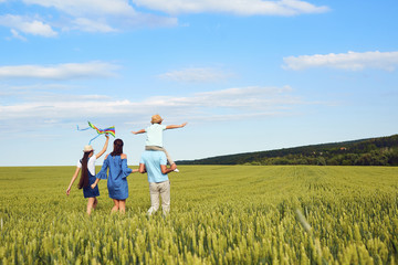 A happy family is walking in a wheat field in the summer. Back view.