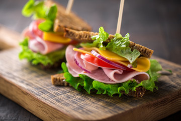 breakfast sandwich with salad, ham, cheese and tomato