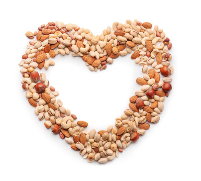Heart made of different nuts on white background