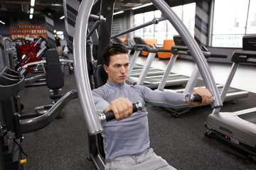 Young man training in modern gym