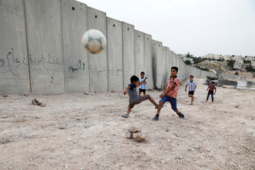 Nassim Ammour scores a goal as he plays with friends next to the Israeli barrier in the Shuafat refugee camp in East Jerusalem