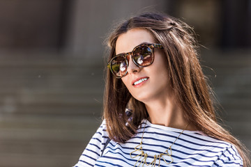 portrait of of beautiful young woman in sunglasses on street