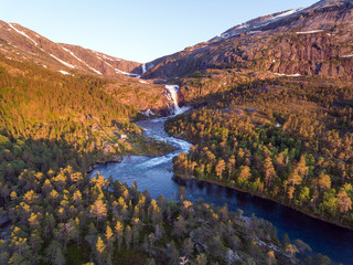 Photo of Rapid Stunning Waterfall in Husedalen Valley, Norway. Aerial view. Summer time.