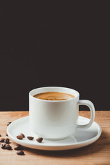 Espresso coffee cup on wooden table and dark background