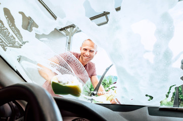 Man washes his car front window inside the car camera view