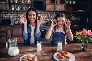 daughter and mother holding cookies in the hands