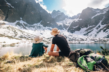 Father and son backpackers sit near the mountain lakeу encircled snowy peaks