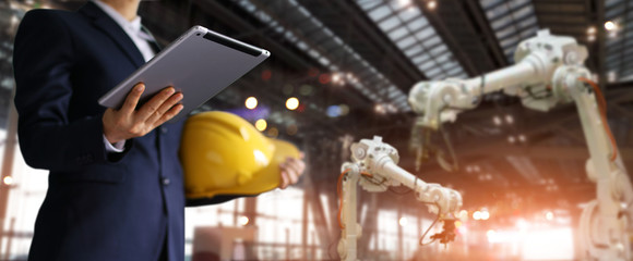Businessman in a future construction site, Robotics engineer using tablet with control industrial robotics, Automation robot arms machine in intelligent factory industrial. Industry 4.0 concept