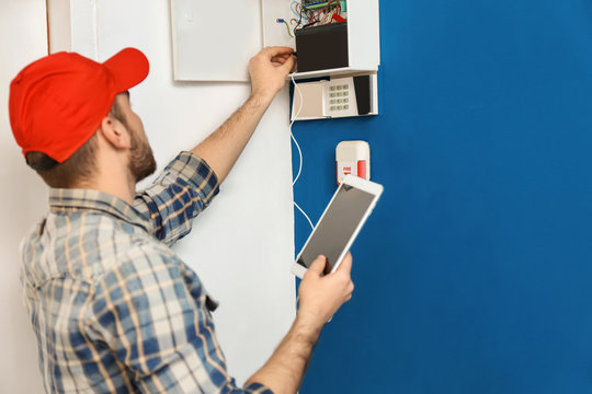 Young electrician installing alarm system