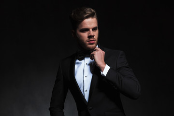 portrait of pensive elegant man in tuxedo looking to side