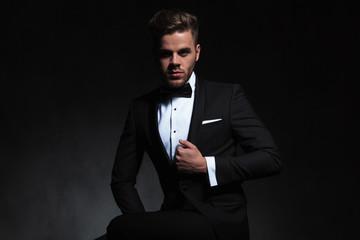 handsome man wearing black tuxedo posing while holding suit collar