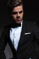portrait of handsome young man in tuxedo looking to side