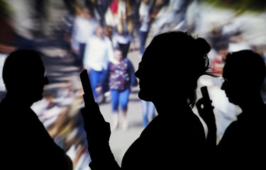 People look at data on their mobiles as background with crowd of people walking is projected in this illustration picture