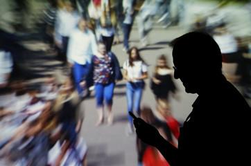 A man looks at data on his mobile as background with crowd of people walking is projected in this picture illustration