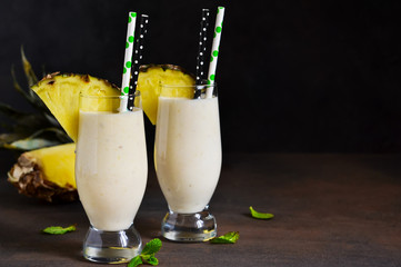 Milk cocktail with vanilla ice cream, pineapple and mango on a dark background.