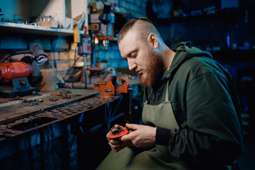 Man with beard in overalls makes details of iron and wood in garage workshop, handmade production. concept is professional jeweler.