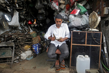 A man reads the Koran inside his shop selling second-hand automobile parts during the holy month of Ramadan in Mumbai
