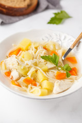 Chicken soup with noodles and vegetables in a white plate.