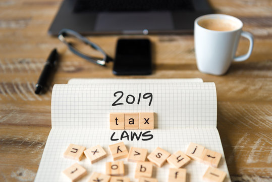 Closeup on notebook over vintage desk background, front focus on wooden blocks with letters making 2019 Tax Laws text
