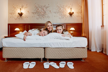 Happy mother and children twins hugging in bed, in a cozy hotel room.