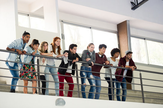 Group of students standing together on mezzanine, watching event