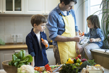 young father is cooking with son and daughter