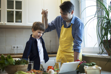 Father and son cooking healthy food and hit their open hands, celebrating