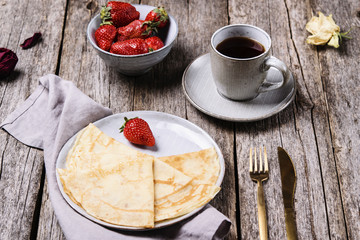 Openwork thin cheese crepes served with strawberry on wooden background. Homemade pancakes. Delicious breakfast