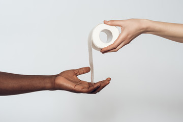 White hand giving toilet paper to black hand.