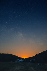 a beautiful view of the starry sky, and mountains, the sky full of stars, great panorama, in the foreground cars and a trailer for a boat, vertical photo