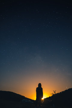 alone woman silhouette in mountains, girl wrapped up in a plaid looks at the sky, enjoying view of amazing night sky full of stars, vertical photo